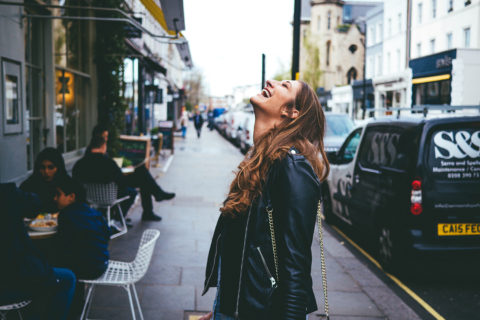 Young woman in leather jacket laughing