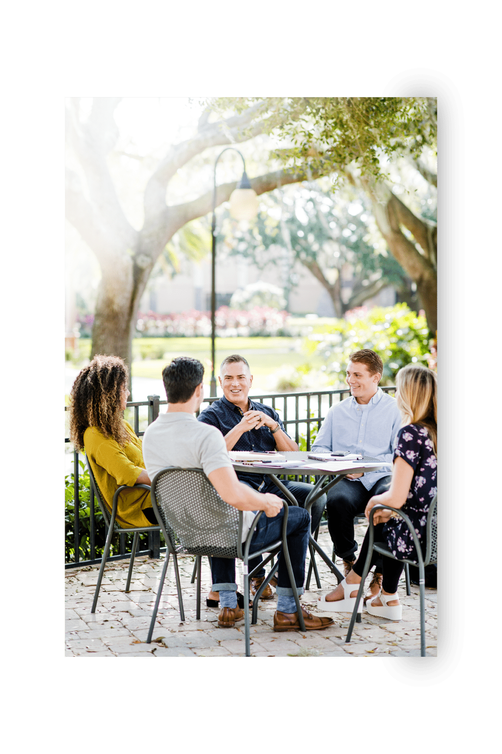 Kent Ingle sitting with SEU students outside under a tree