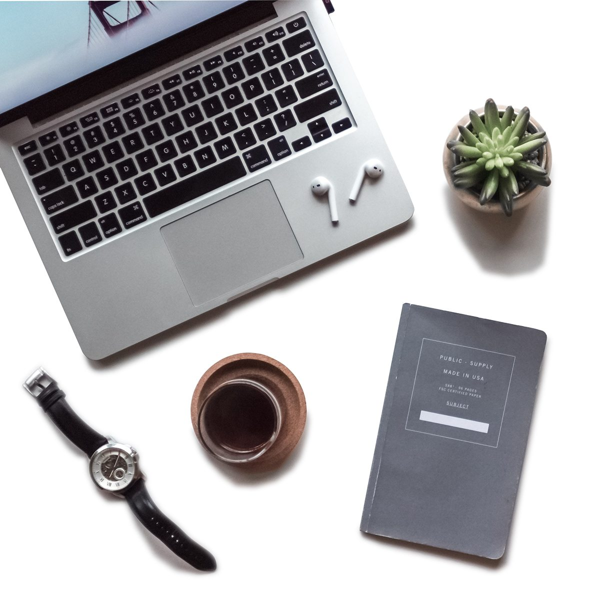 White desk with a watch, cup of coffee, cactus plant, laptop and notebook featured