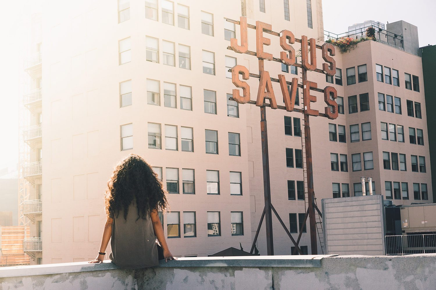 Woman looking at a Jesus Saves sign