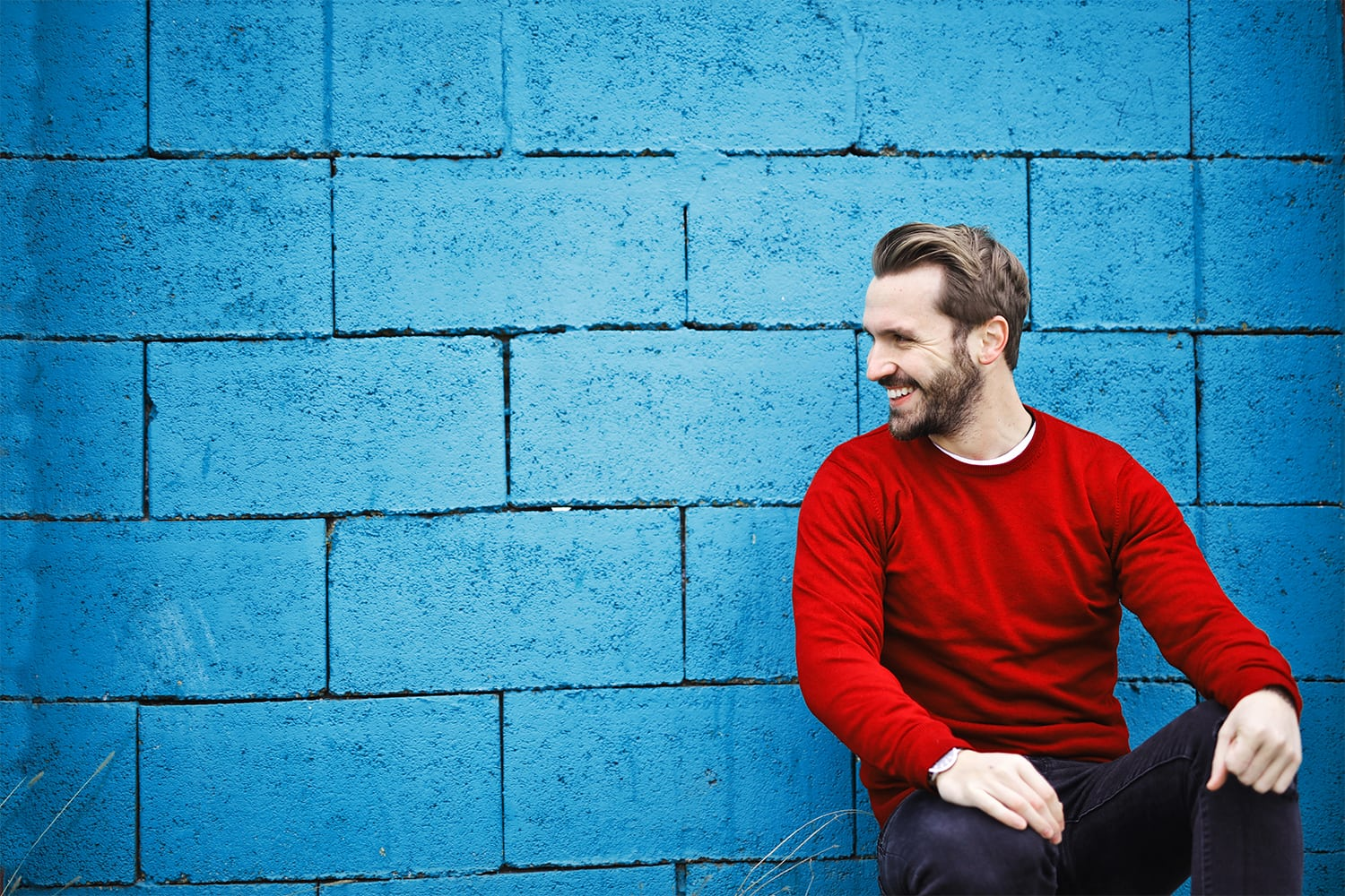 Man smiling sitting against blue wall