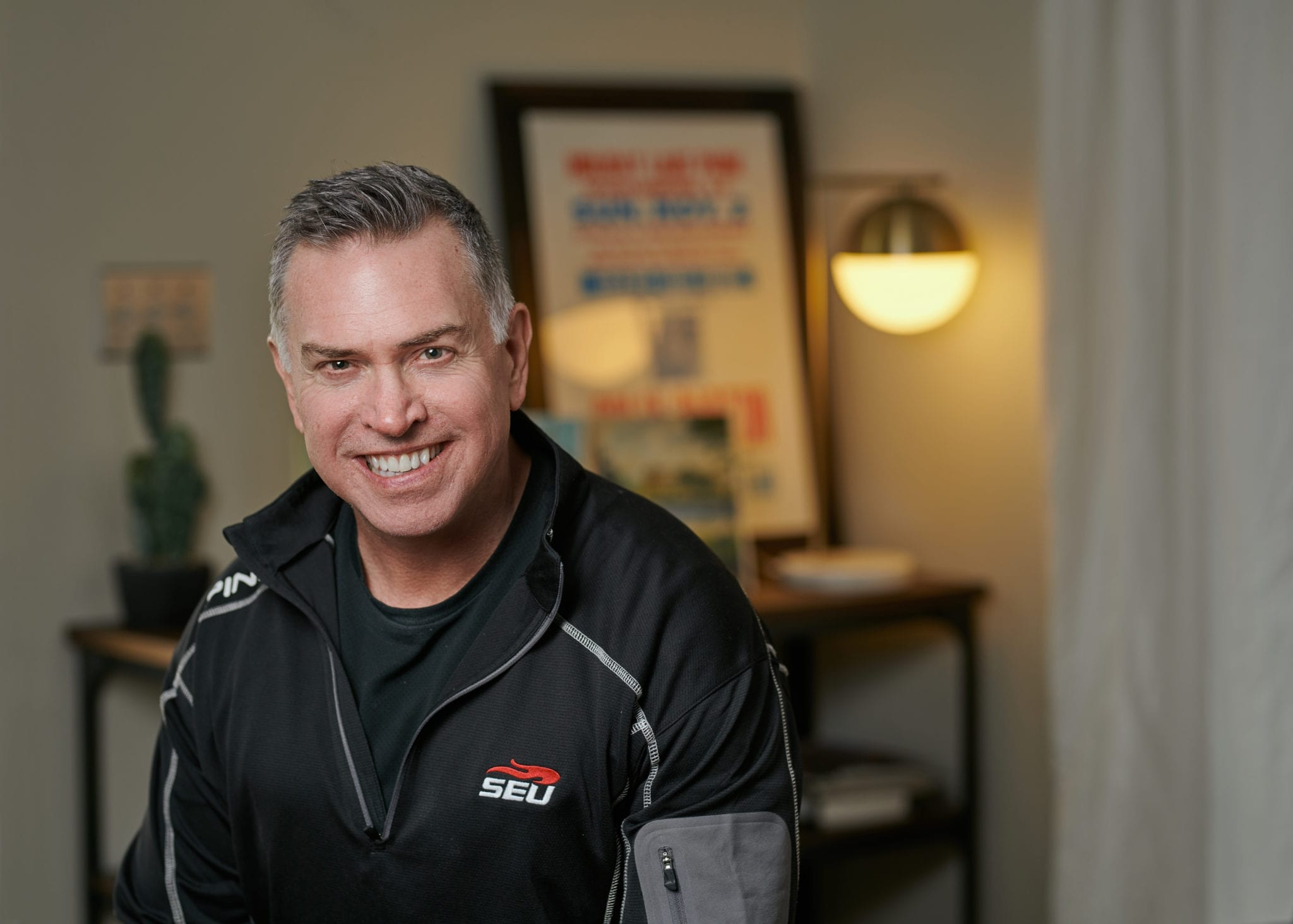 Smiling photo of Kent Ingle wearing a Southeastern University zip sweater.